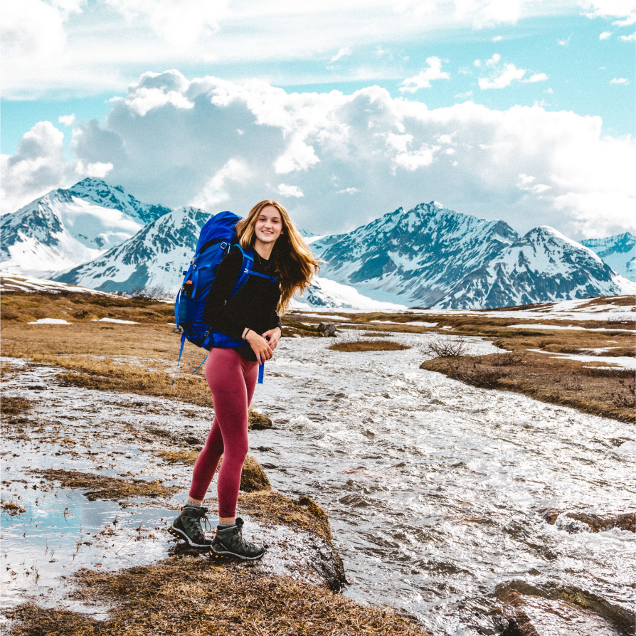 a girl with a backpack standing beside a stream with big mountains in the background