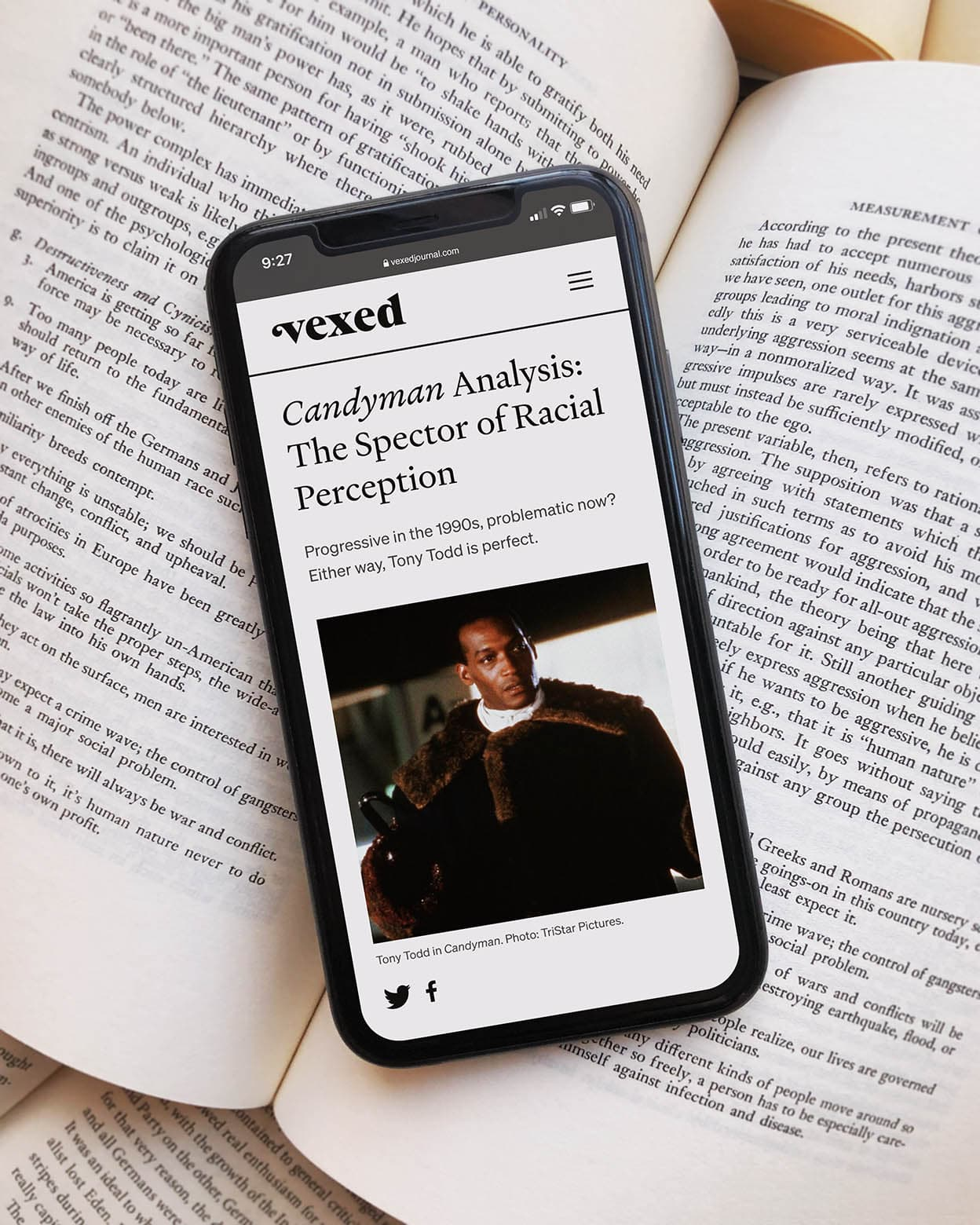 The Vexed website mocked up on a mobile phone, sitting on top of an opened history book.