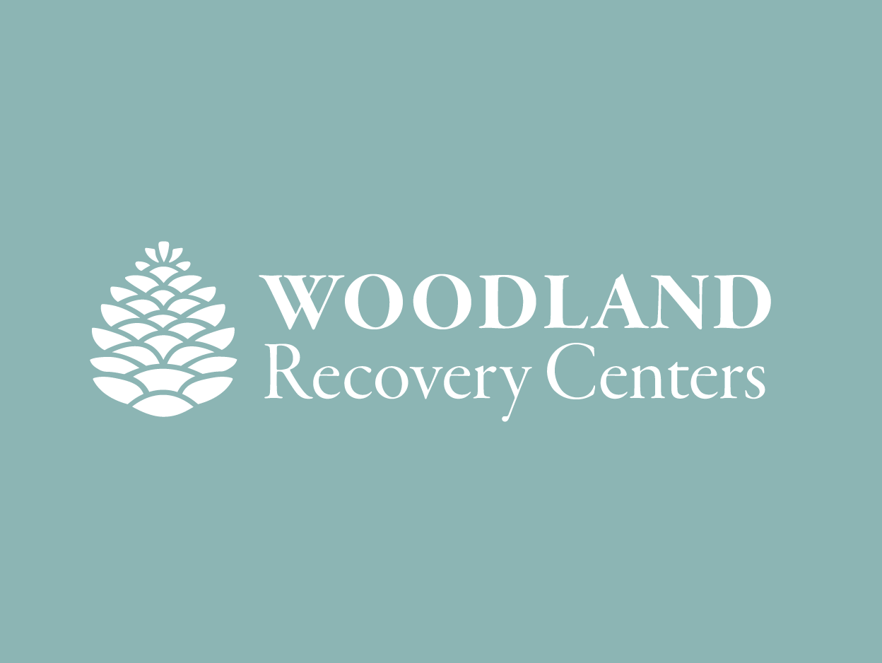 """A white logotype that says """"Woodland Recovery Centers"""" on a sea-foam green background."""