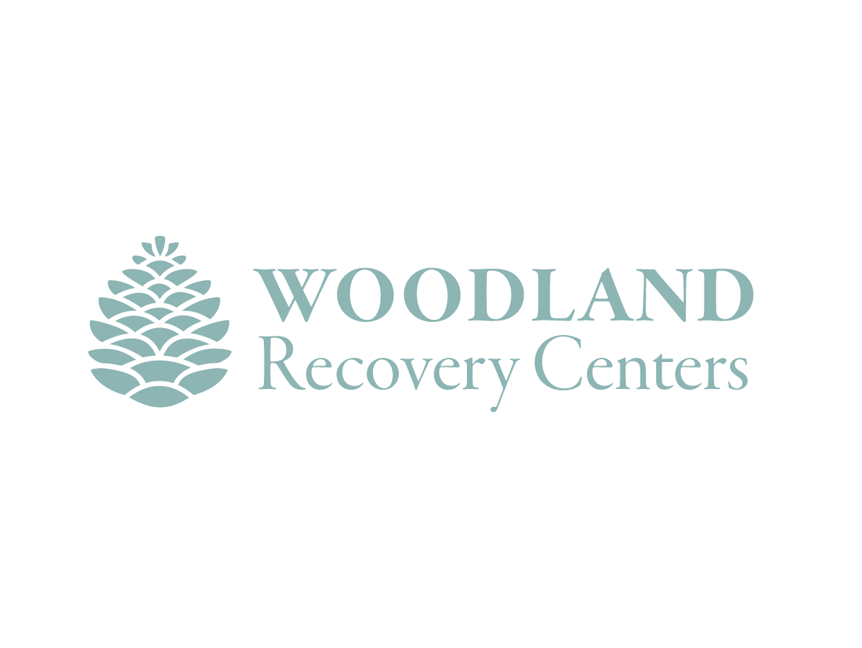 """A sea-foam green logotype that says """"Woodland Recovery Centers."""""""