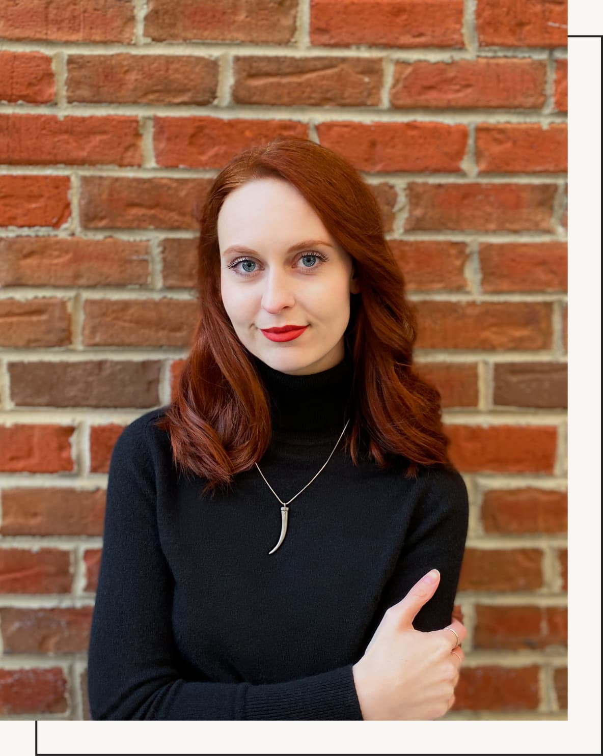 A photo of Katie Lively standing in front of a red brick wall.