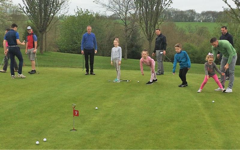 young juniors receiving some coaching on putting green