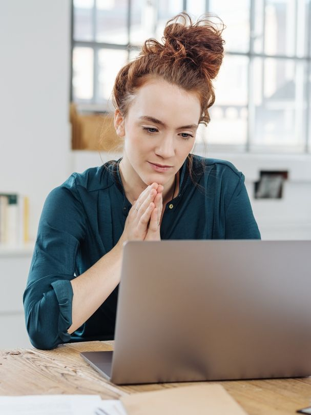 Attraktive junge Geschäftsfrau, die mit einem nachdenklichen Ausdruck auf ihren Laptop an einem Bürotisch schaut.