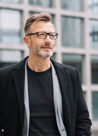 Straßenporträt eines reifen Geschäftsmanns, der eine Brille und einen schwarzen Mantel trägt.