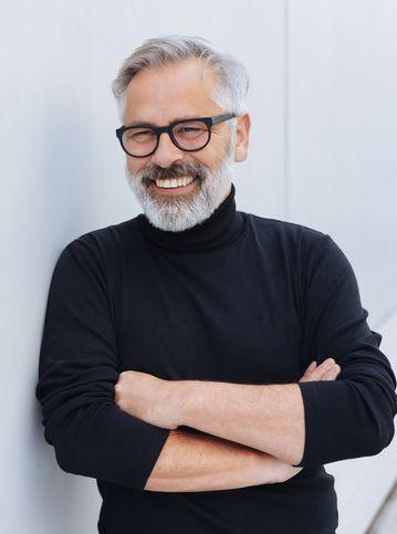 Entspannter, selbstbewusster älterer männlicher Coach mit Bart und Brille, der mit verschränkten Armen vor einer weißen Wand steht.