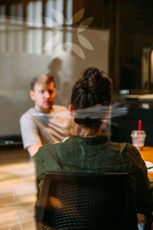 Weiblicher Coach und männlicher Klient bei einem Gespräch in einem Café.