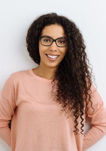 Weiblicher Coach mit afrikanischer Herkunft, der vor einer weißen Hintergrundwand in die Kamera  lächelt.