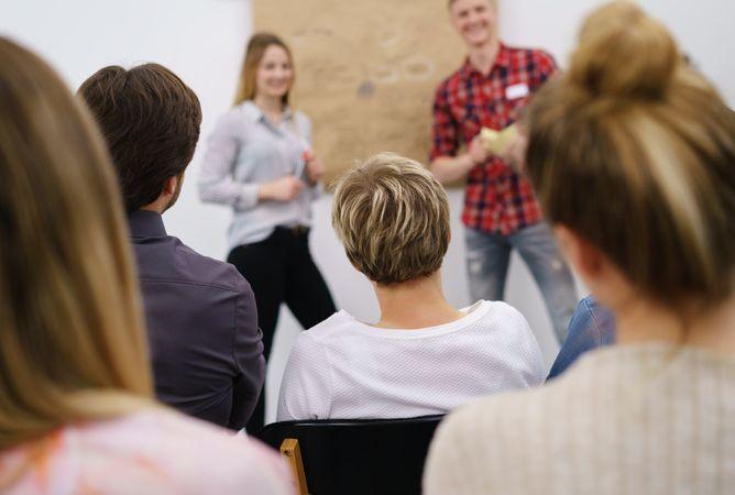 Eine Gruppe, die von hinten mit Fokus auf den Hinterkopf betrachtet wird, hört einem Vortrag zu. Außerhalb des Fokus sind im Hintergrund zwei stehende, der Gruppe zugewandten Personen zu erkennen.
