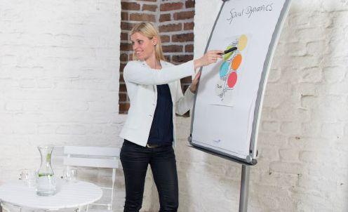Eine junge Frau zeigt auf ein Whiteboard und richtet sich jemandem zu, der nicht im Bild ist.