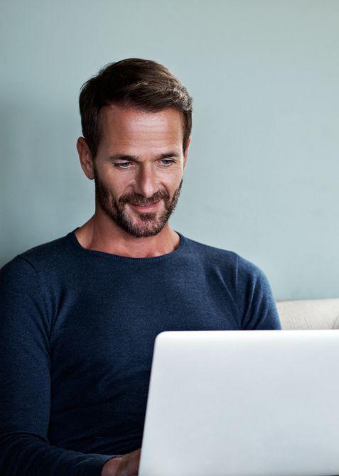 Angeschnittenes Bild eines männlichen Coaches, der seinen Laptop benutzt, während er auf einer Couch sitzt.