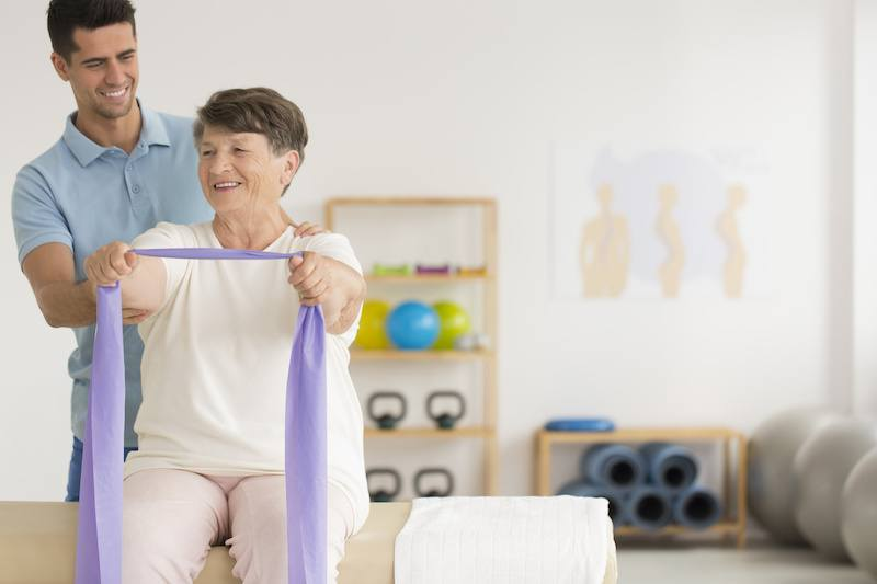 Physiotherapist helping older lady exercise in a private gym clinic