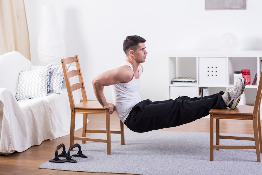 Person exercising from home with chairs doing a dip