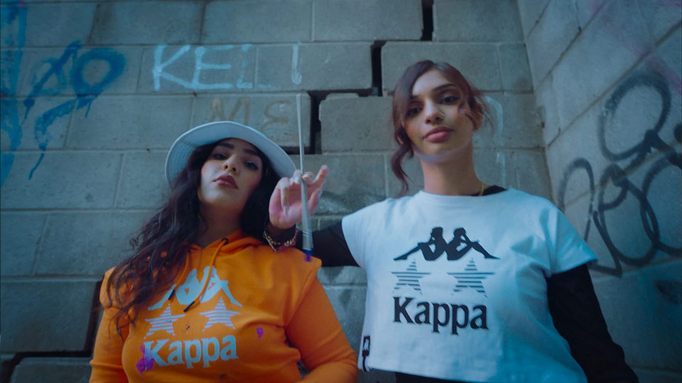 Two young women gaze at the camera wearing Kappa shirts in front of a cement brick wall with graffiti