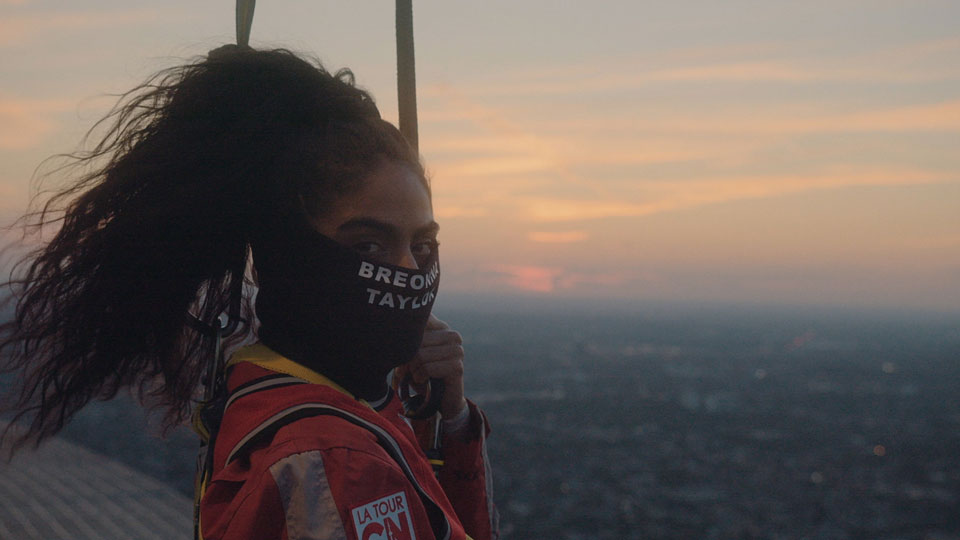 Jessie Reyez gazes at the camera from atop a large building at dusk