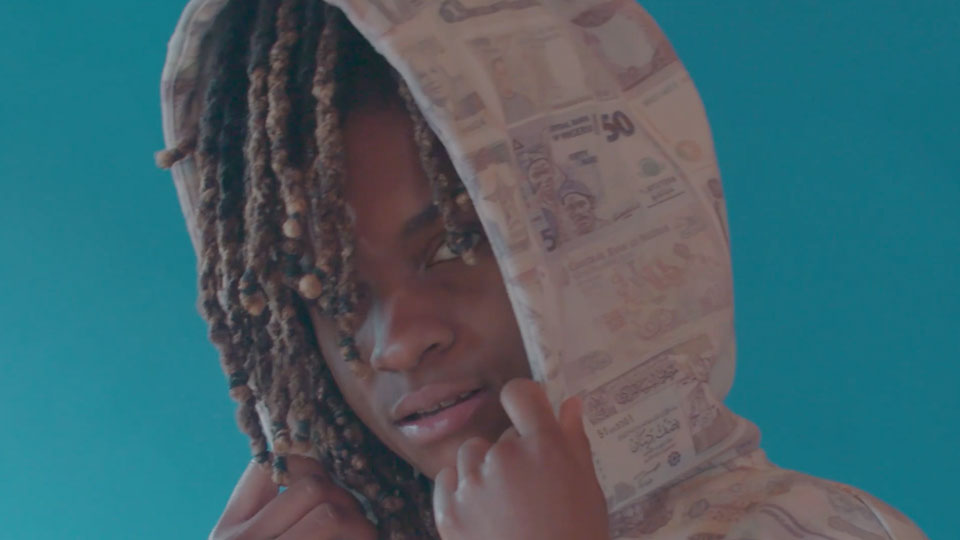 Koffee looks at the camera with a sweatshirt on over his head