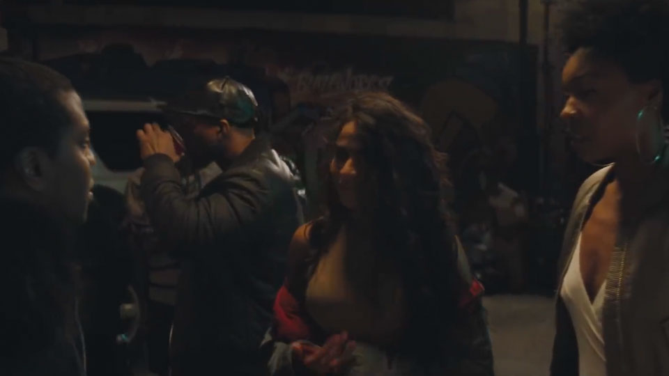Jessie Reyez walks outside through a group of people at night