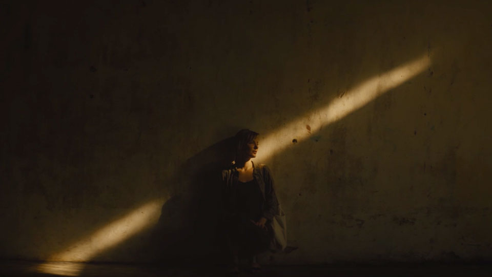 Woman leans against wall with a thin line of light cuts angularly through the scene at night