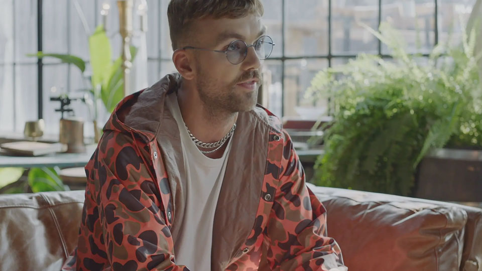 Sonreal sitting in a brightly lit space peering off into the distance