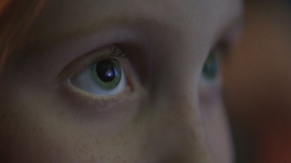 Close up shot of a young girls eyes looking upward and to the right of the camera