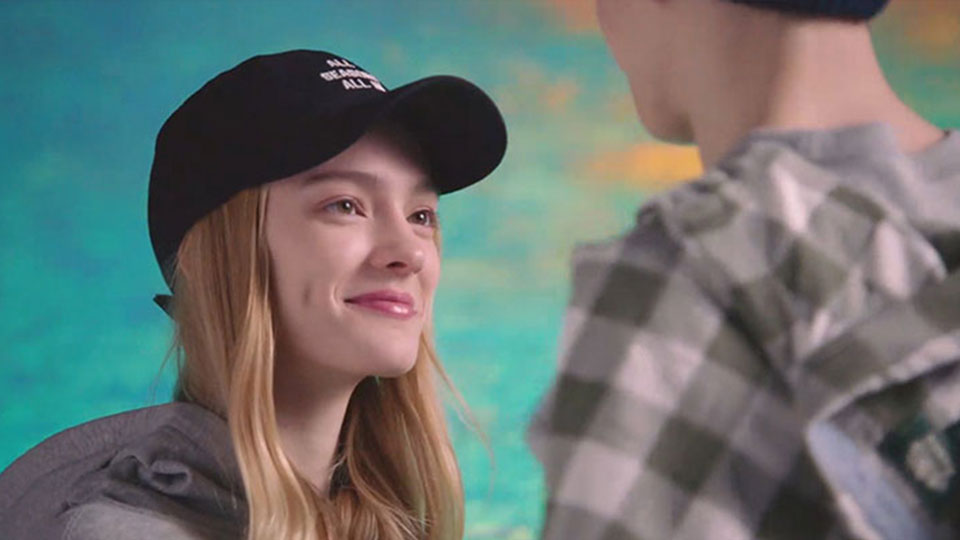 Girl with a hat gazes at a boy in front of a bright teal backdrop