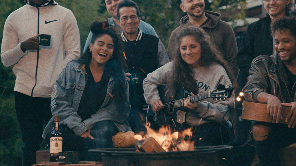 Jessie Reyez and a group of people sit in front of a campfire while she plays music