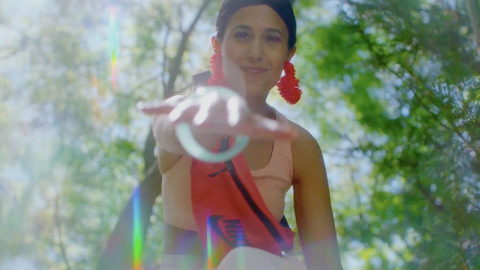 Woman reaches hand to the camera in front of a tree with bold colorful clothes and rainbow light rays