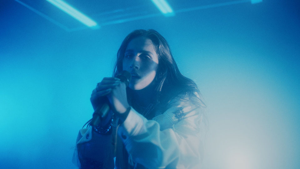Tate singing a song on stage with bright blue lights with atmospheric fog