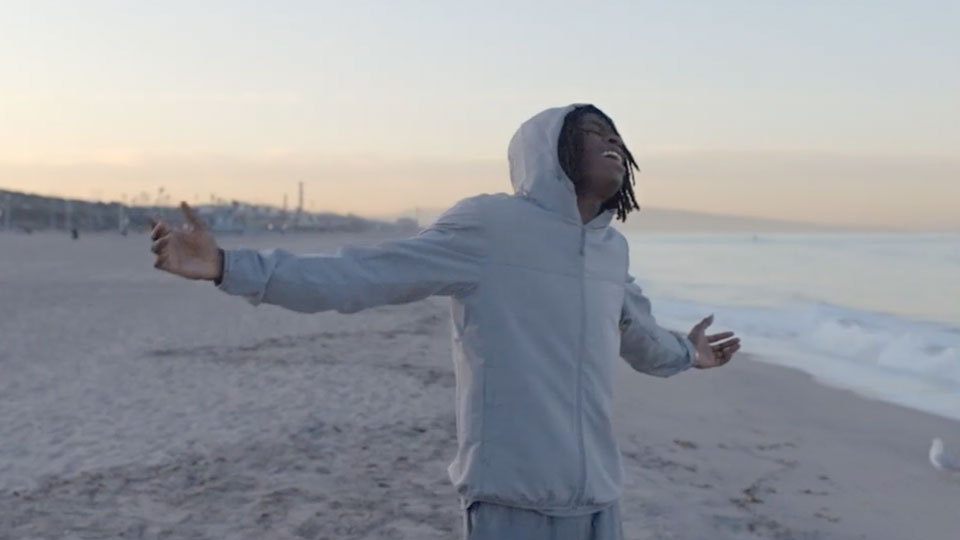 Daniel Caesar stands with his arms open wide on a beach during sunrise or sunset