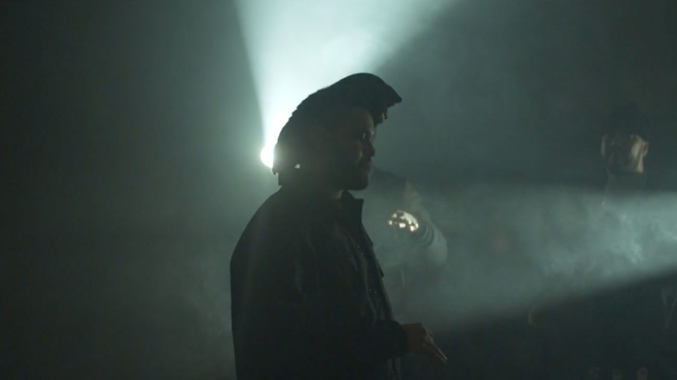 The Weeknd stands in a silhouette behind light projectors and fog machines