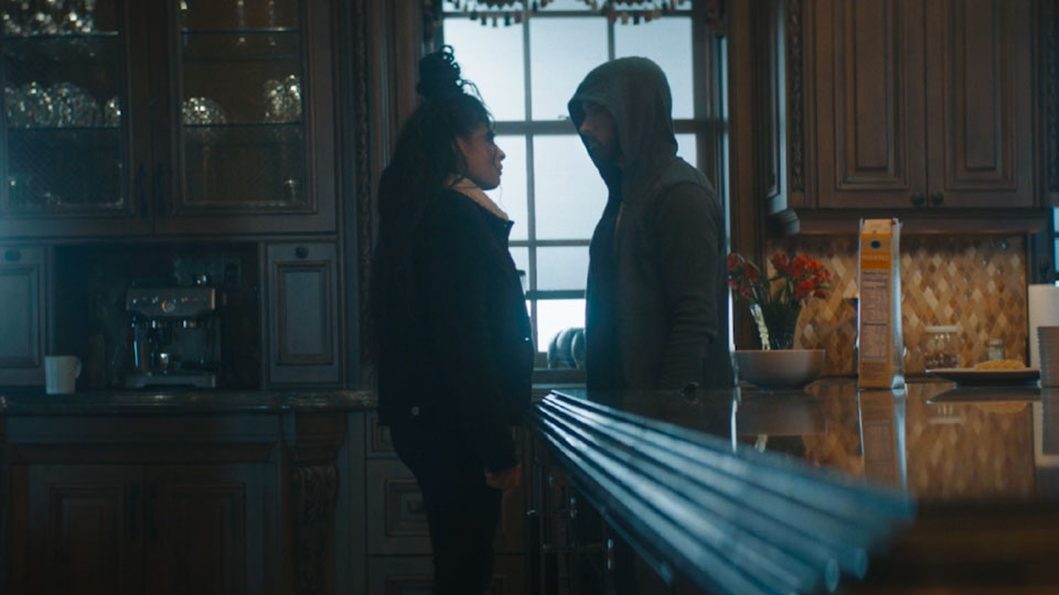 Jessie and Eminem stand facing one another at the end of a bar