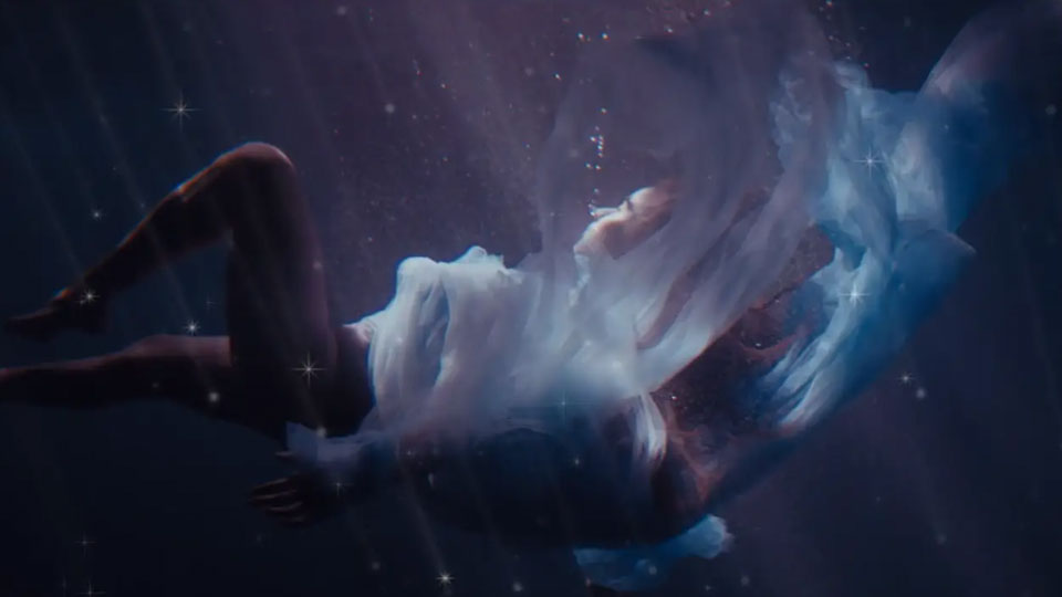 Jessie Reyez lays underwater with loose fabric and soft blues and lavender color fills the scene