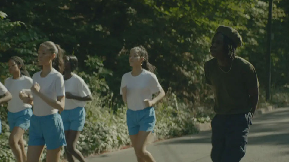 Women running on a street while Daniel Caesar stands with his arms behind his back