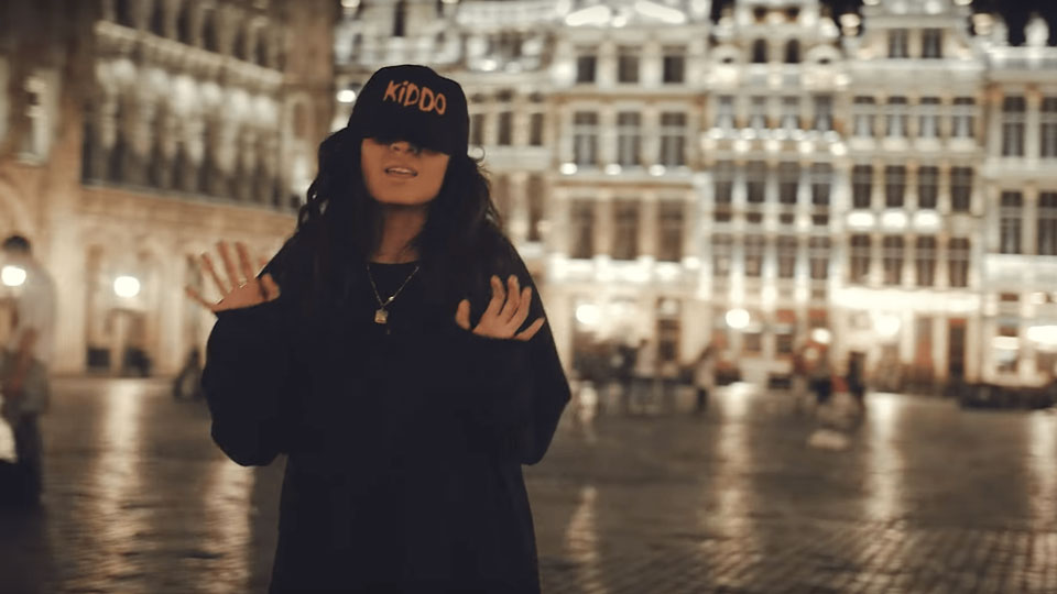 Jessie Reyez stands on a city center area at night