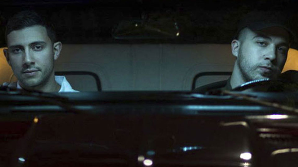 Two men sit in a car at night lit up by lights gazing through the front window of the car at the camera