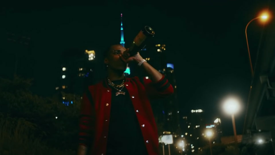 Roy Woods on the sidewalk walking at night in a city while drinking from a bottle of bubbly