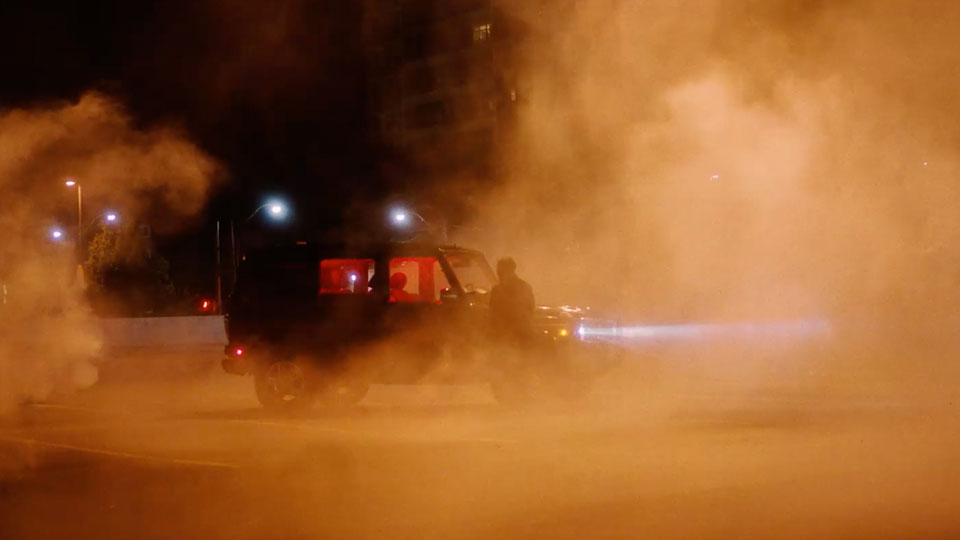 Night scene of a car with lights on and a bright orange smoke or fog being lit up by a streetlight.