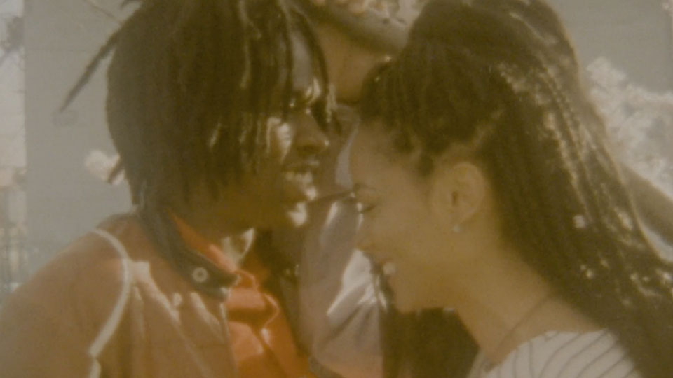 Daniel Caesar smiles and embraces a women. Warm colors and vintage film texture in the image.