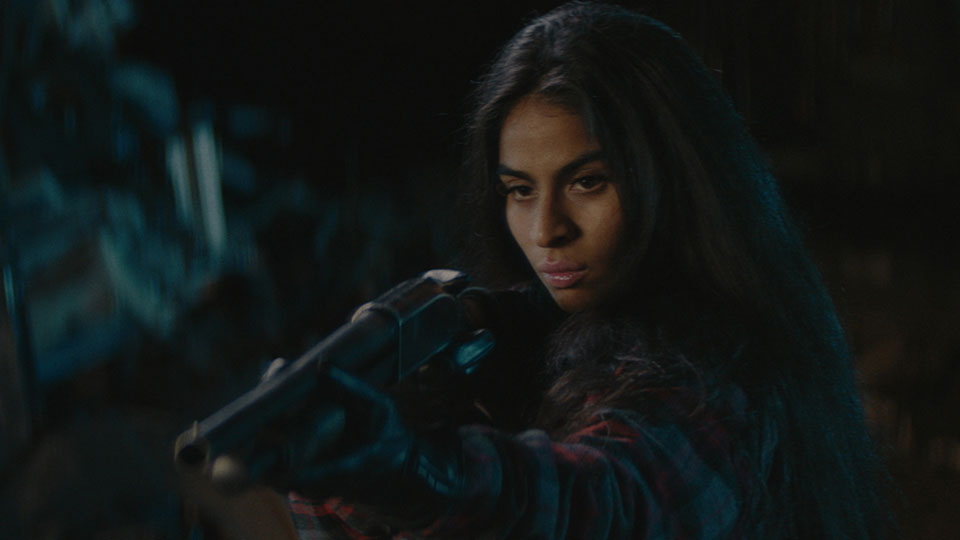 Jessie Reyez is facing forward, pointing a gun downward to the left of frame with a serious expression on her face.