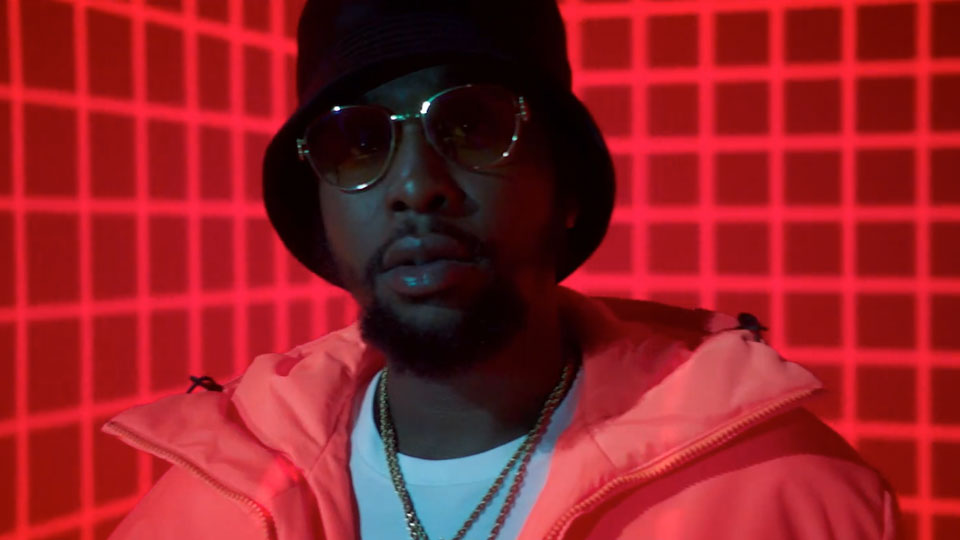 Popcaan gazing at the camera dressed in glasses, a hat, and bright jacket in front of a neon red grid projected onto the walls.