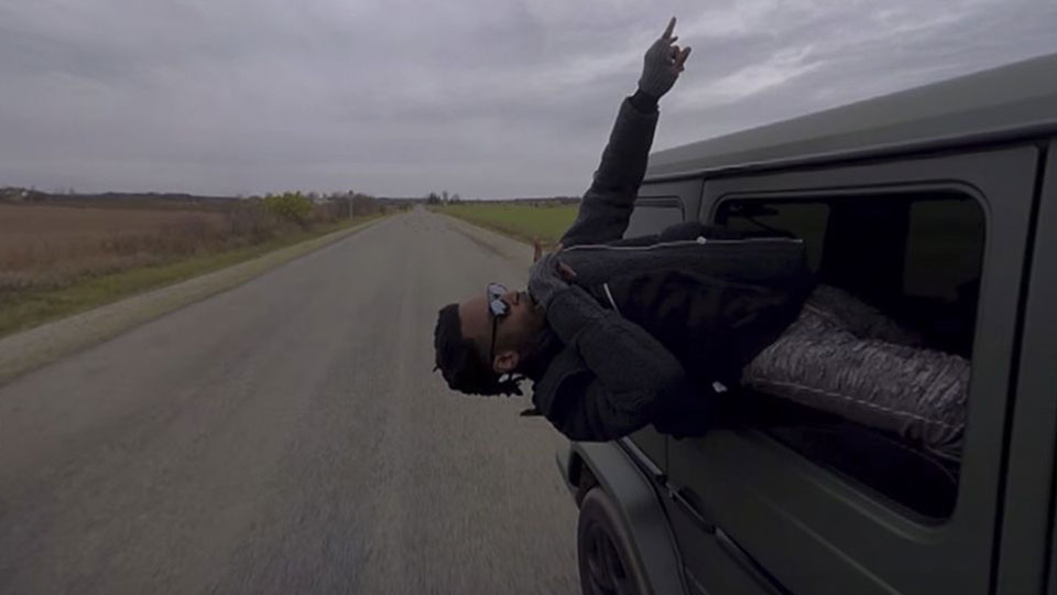 Man leaning out of the back window of an SUV on a country road pointing to the sky above