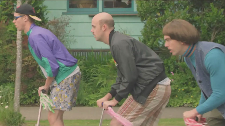 3 men riding scooters with retro clothes in a neighborhood