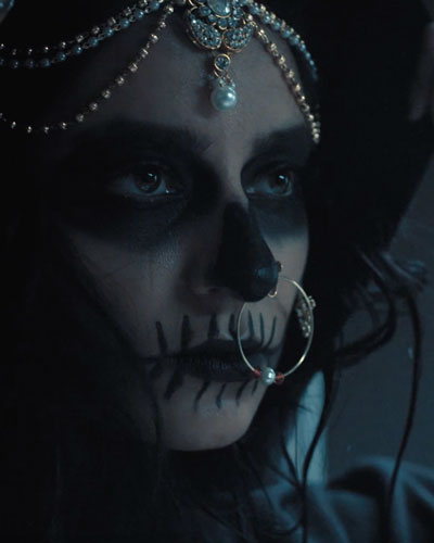 Woman with white and black makeup with jewelry on her forehead