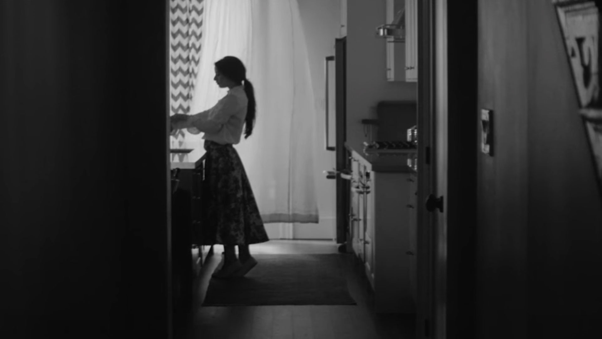 Black and white photo of a woman in a kitchen in the distance from the hallway