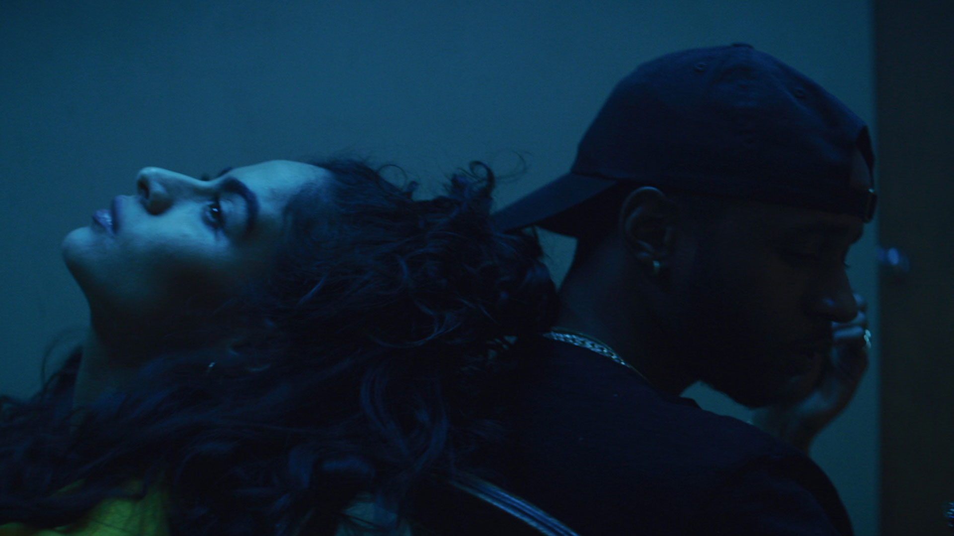 Under a deep blue lighting at night, Jessie Reyez tips her had back to rest on the shoulder of 6LACK.