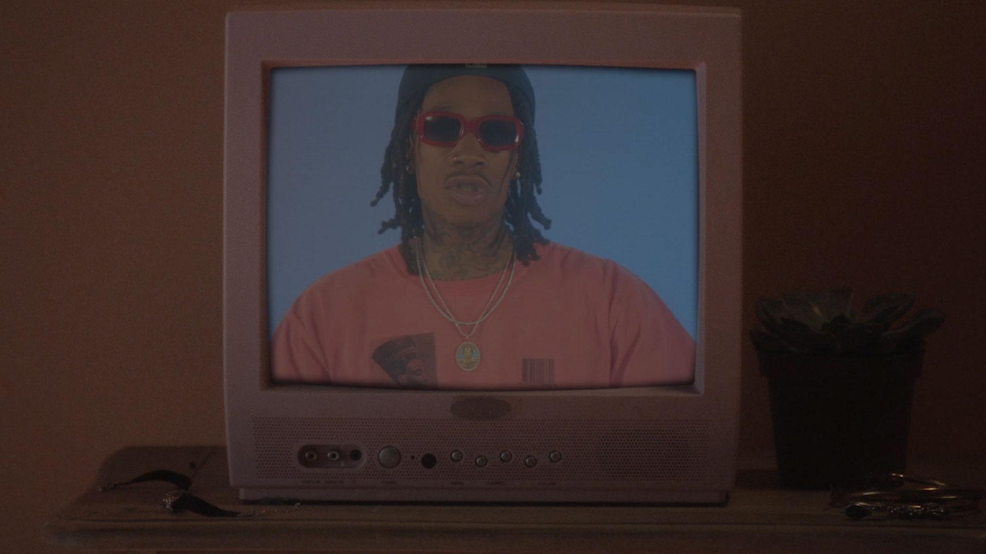 Wiz Khalifa is on an old monitor screen facing the camera under moody orange tones