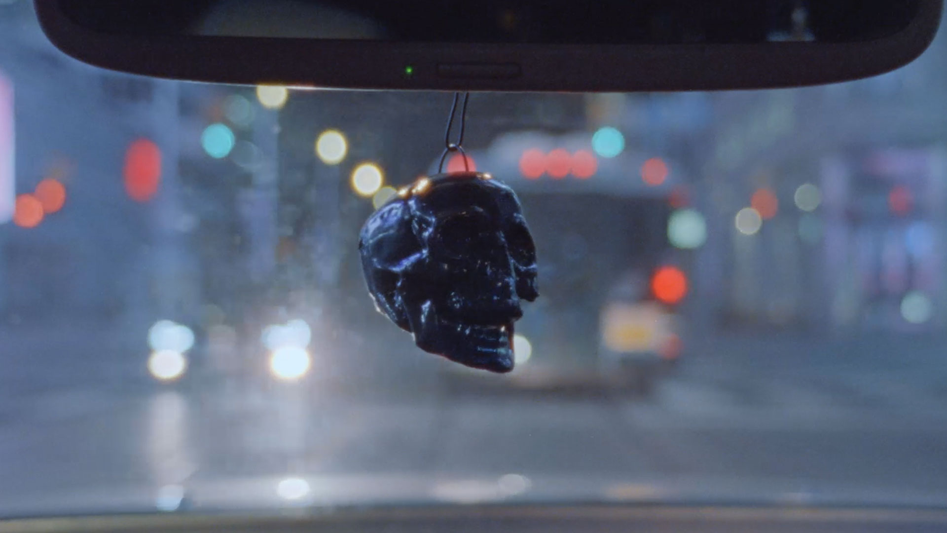 Metal skull hangs from the rearview mirror shot on a city street at night