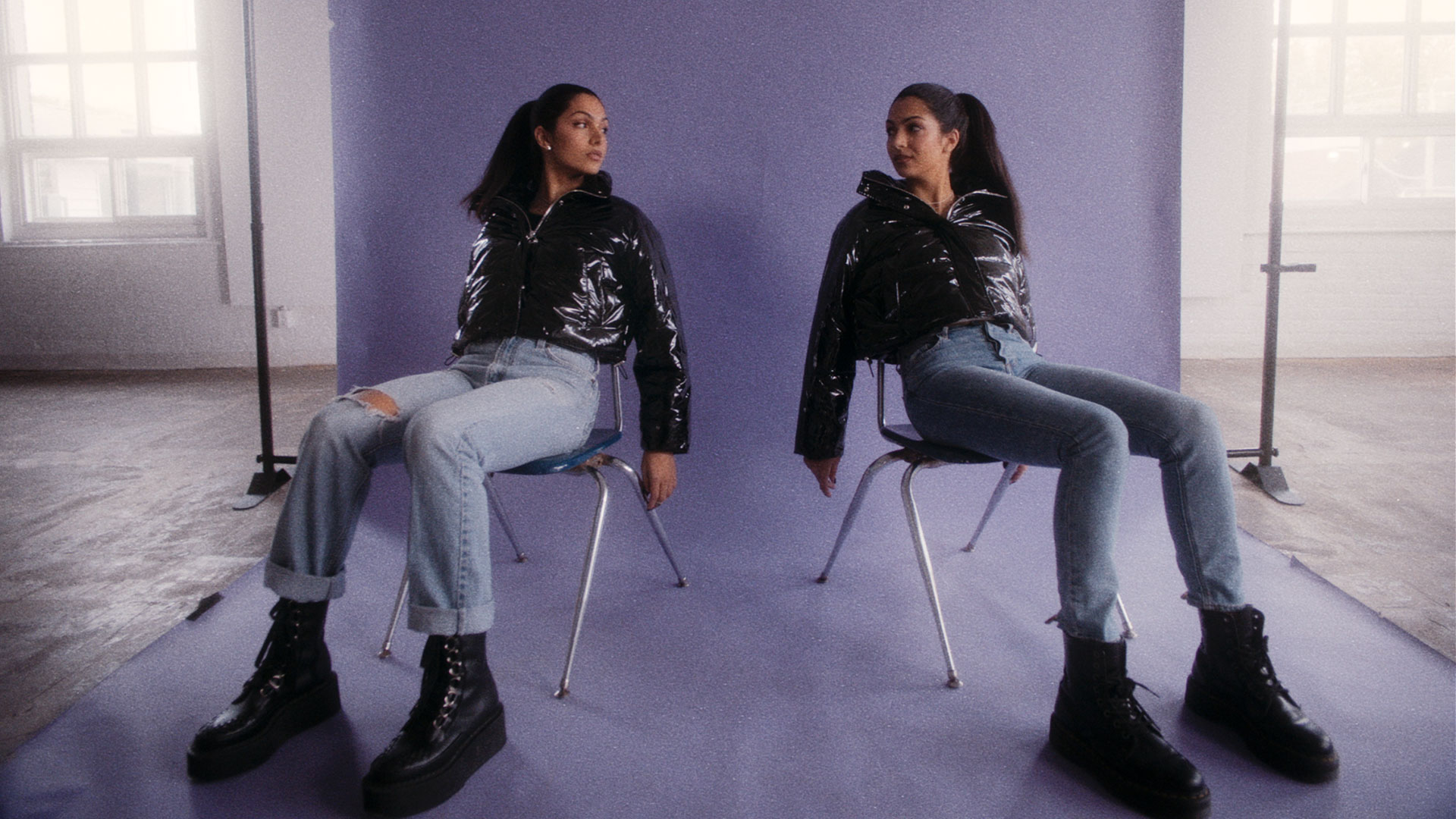 Two woman pose sitting down in chairs facing 45 degree angle away from one another in front of a lavender photoshoot backdrop in a studio