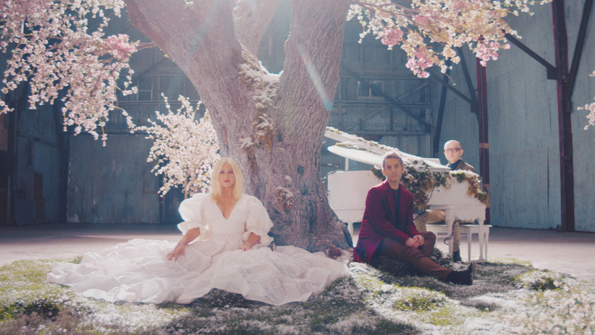 Christina Aguilera and A Great Big World sit underneath a blooming tree inside a large building