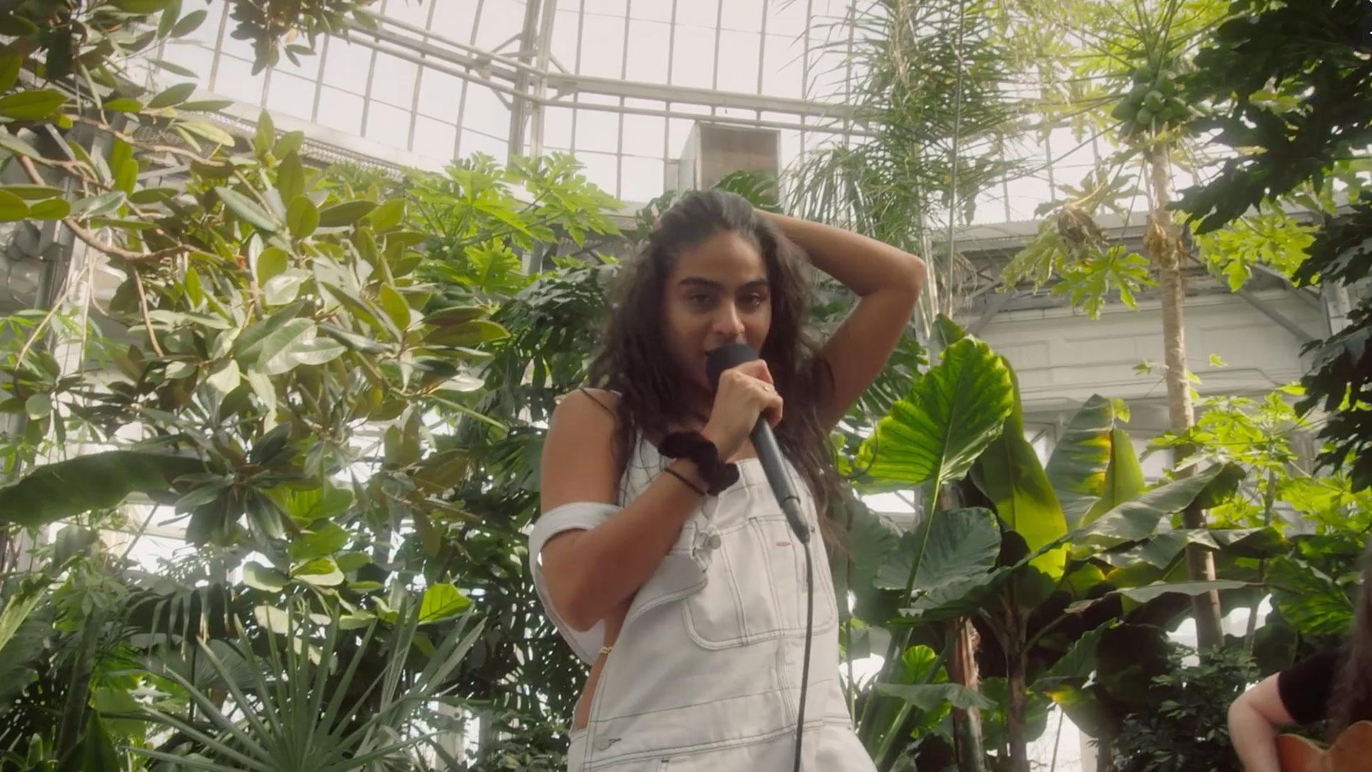 Jessie Reyez singing in front of plants