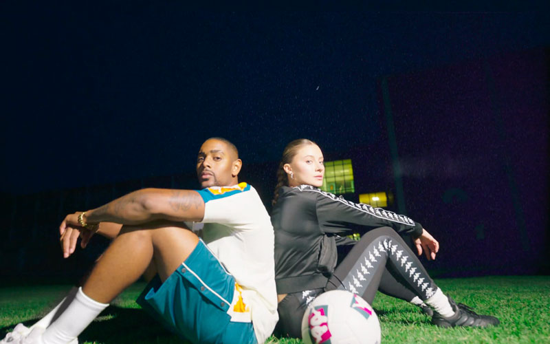 Two people sitting on an athletic field at night leaning against one another